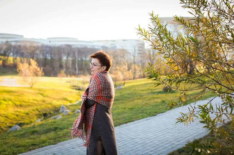 Portrait of carefree caucasian woman with short haircut in warm casual clothes at autumn park in selective focus stock photos