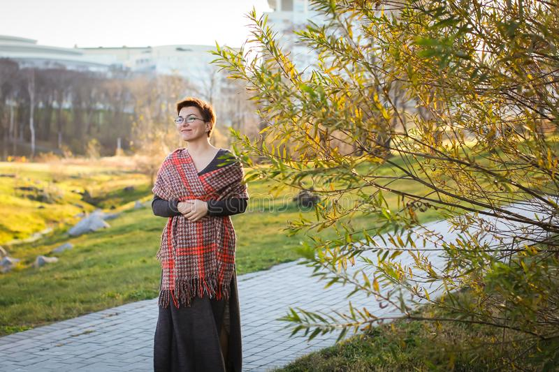 Portrait of carefree caucasian woman with short haircut in warm casual clothes at autumn park in selective focus stock image