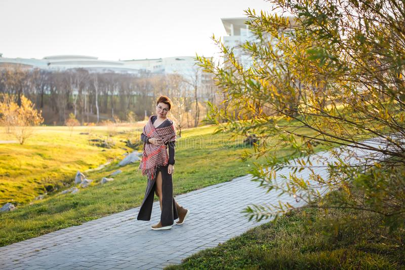 Portrait of carefree caucasian woman with short haircut in warm casual clothes at autumn park in selective focus royalty free stock image