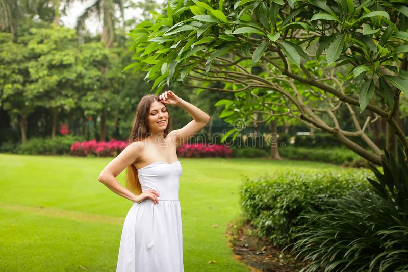 Portrait of carefree young woman in white dress posing in green summer park royalty free stock image