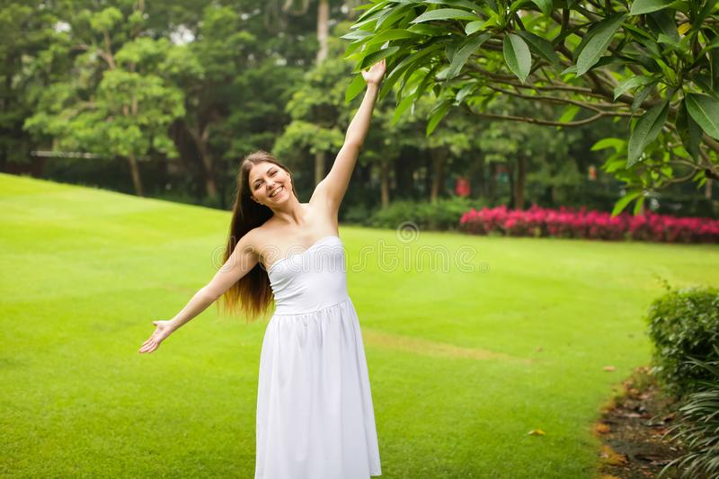 Portrait of carefree young woman in white dress posing in green summer park royalty free stock photo