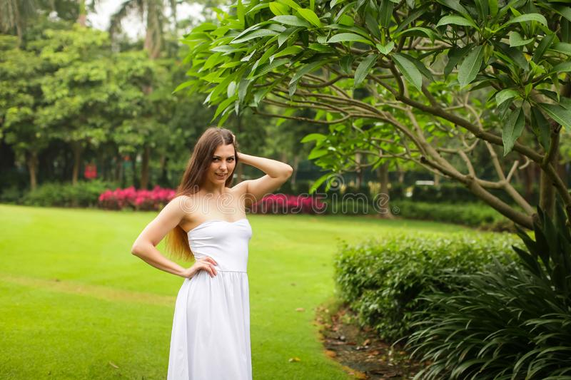 Portrait of carefree young woman in white dress posing in green summer park stock images