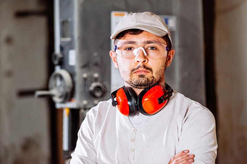 Portrait of carpenter. Carpenter working with Industrial tool in wood factory wearing safety glasses and hearing protection stock photo