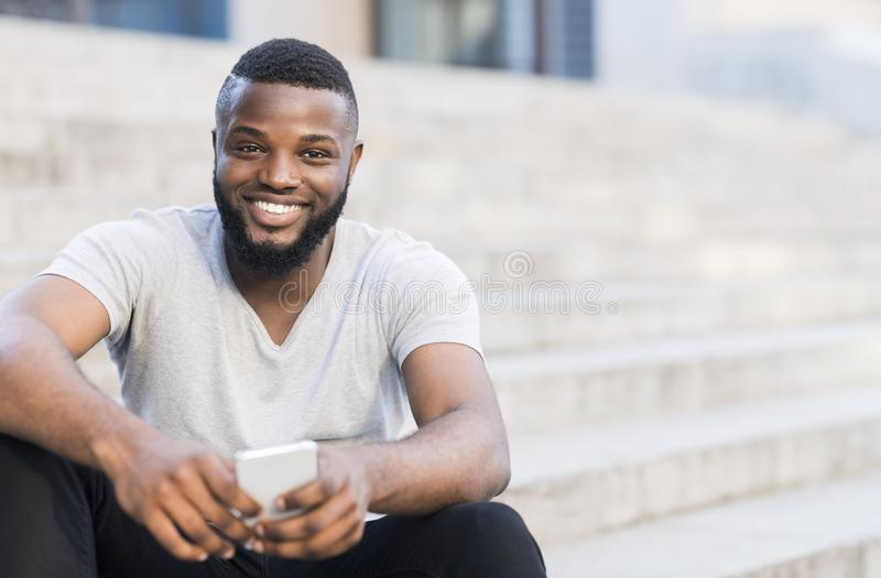 Portrait of casual african guy sitting on stairs and smiling. Outdoor, copy space stock photo