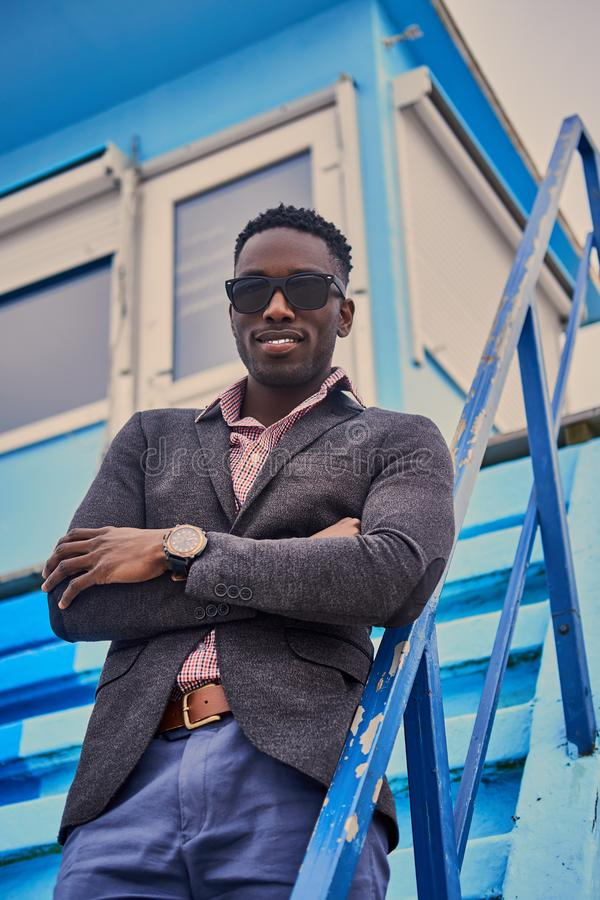 Portrait of casual Black male dressed in a modern suit and sungl royalty free stock image