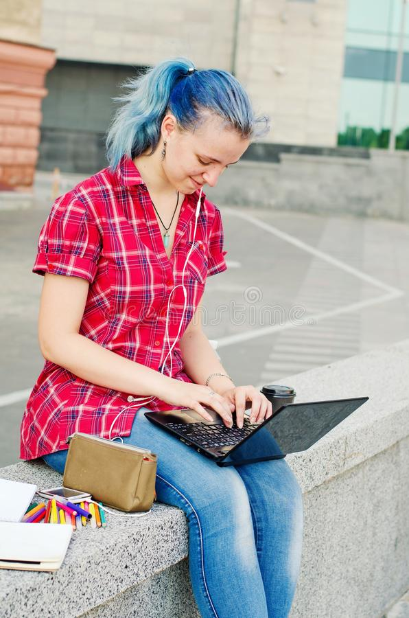Portrait of a casual cute and young girl with blue hair in jeans in urban summer drawing or writing royalty free stock image