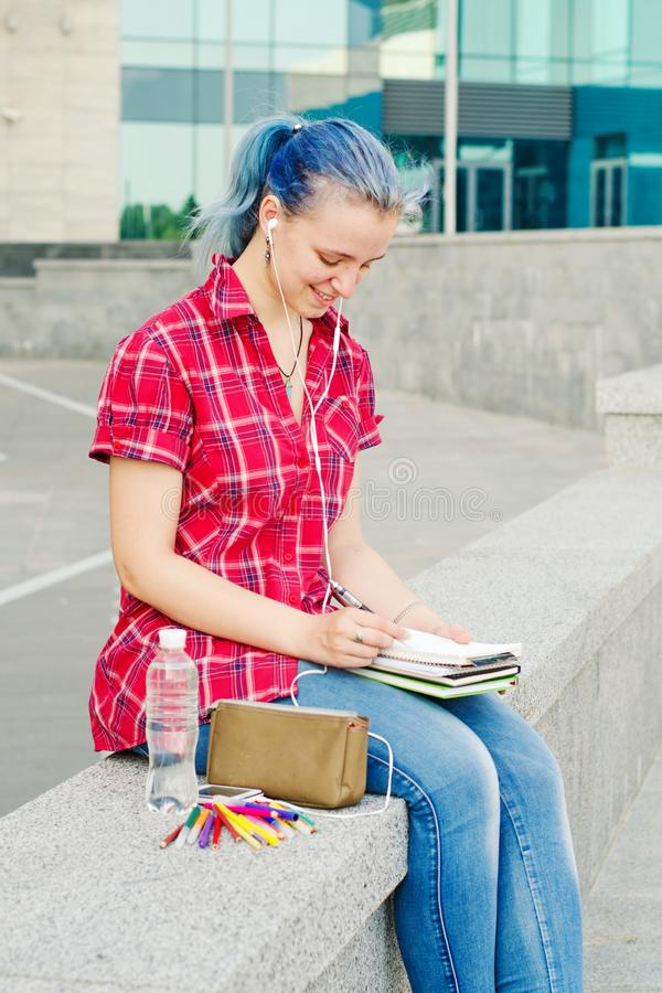 Portrait of a casual cute and young girl with blue hair in jeans in urban summer drawing or writing royalty free stock photo