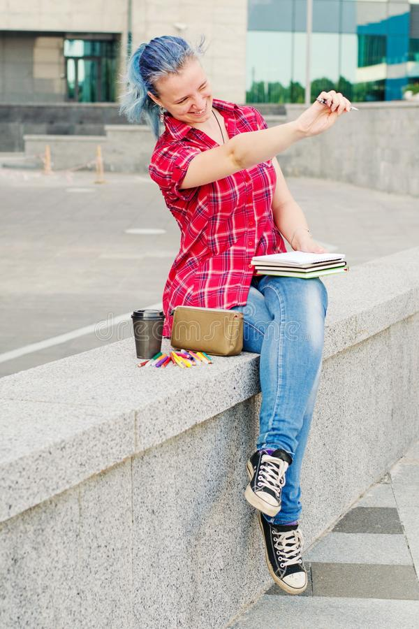 Portrait of a casual cute and young girl with blue hair in jeans in urban summer drawing or writing stock image