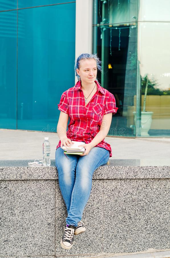 Portrait of a casual cute and young girl with blue hair in jeans in urban summer drawing or writing stock photos