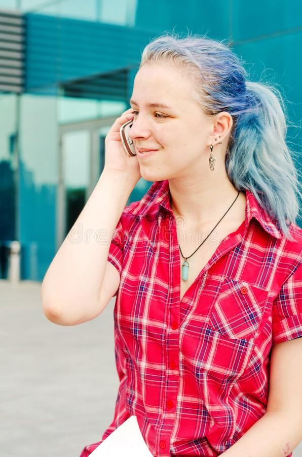 Portrait of a casual cute and young girl with blue hair in the city talking on the phone stock images