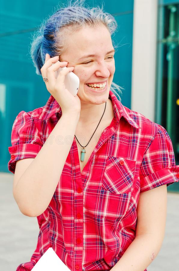 Portrait of a casual cute and young girl with blue hair in the city talking on the phone royalty free stock photography