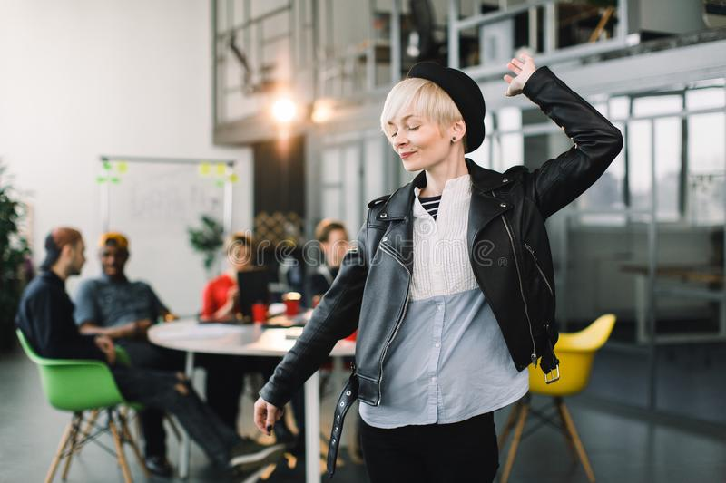 Portrait of a casual female office worker standing with arms up and down, having fun at a bright office, while her five royalty free stock photo