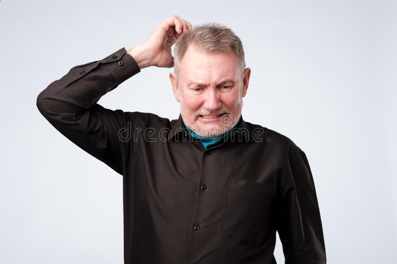 Portrait of casual mature man in black shirt thinking and looking puzzled stock photos