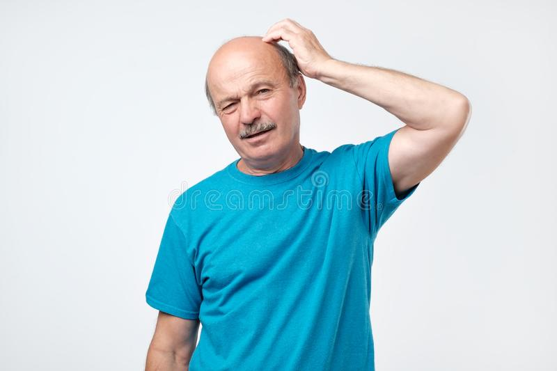 Portrait of casual mature man in blue shirt thinking and looking puzzled royalty free stock photo