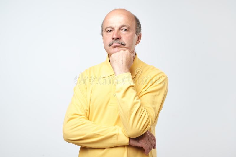 Portrait of casual mature man in yellow shirt thinking and looking puzzled stock images