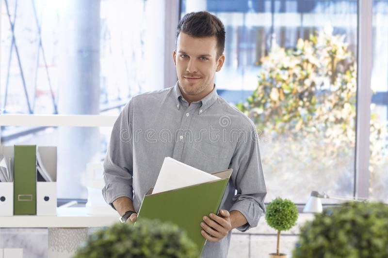 Portrait of casual office worker with folder. Portrait of casual office worker holding folder, smiling in office royalty free stock photography