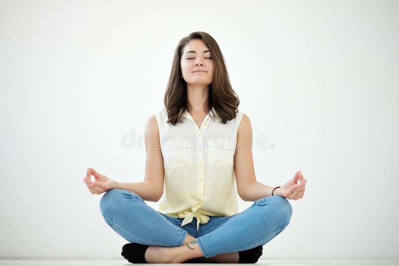 Portrait of a casual pretty woman meditating on the floor on white background royalty free stock image