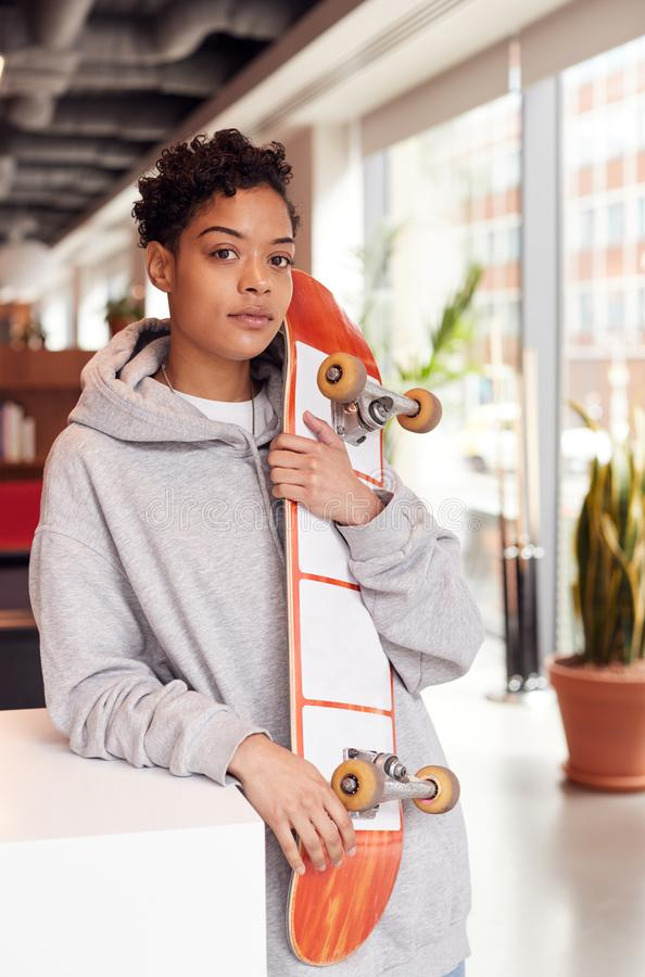 Portrait Of Casually Dressed Young Businesswoman With Skateboard Standing In Open Plan Workplace stock photos