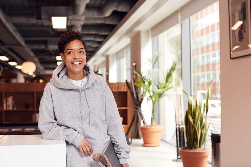 Portrait Of Casually Dressed Young Businesswoman With Skateboard Standing In Open Plan Workplace royalty free stock image