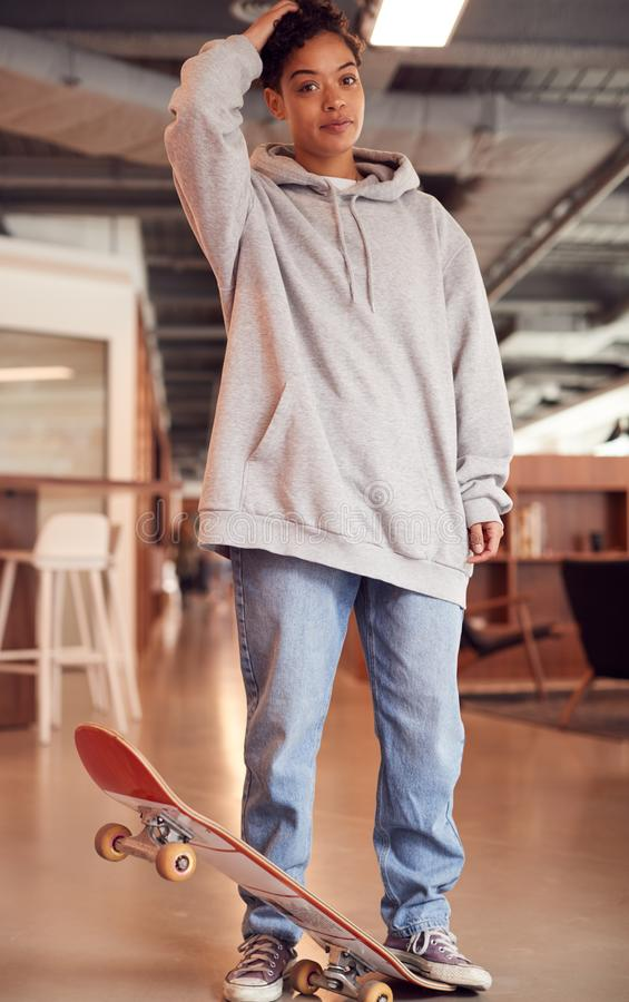 Portrait Of Casually Dressed Young Businesswoman With Skateboard Standing In Open Plan Workplace stock photo