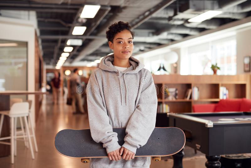 Portrait Of Casually Dressed Young Businesswoman With Skateboard Standing In Open Plan Workplace royalty free stock photo