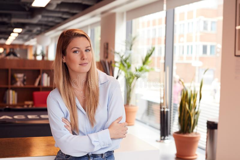 Portrait Of Casually Dressed Young Businesswoman Standing In Modern Open Plan Workplace royalty free stock image