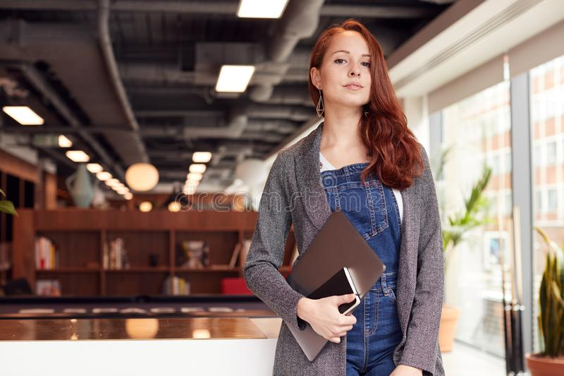 Portrait Of Casually Dressed Young Businesswoman Standing In Modern Open Plan Workplace royalty free stock photography