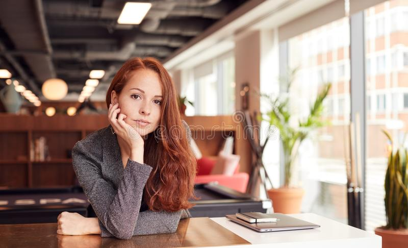 Portrait Of Casually Dressed Young Businesswoman Working At Desk In Modern Open Plan Workplace stock photos