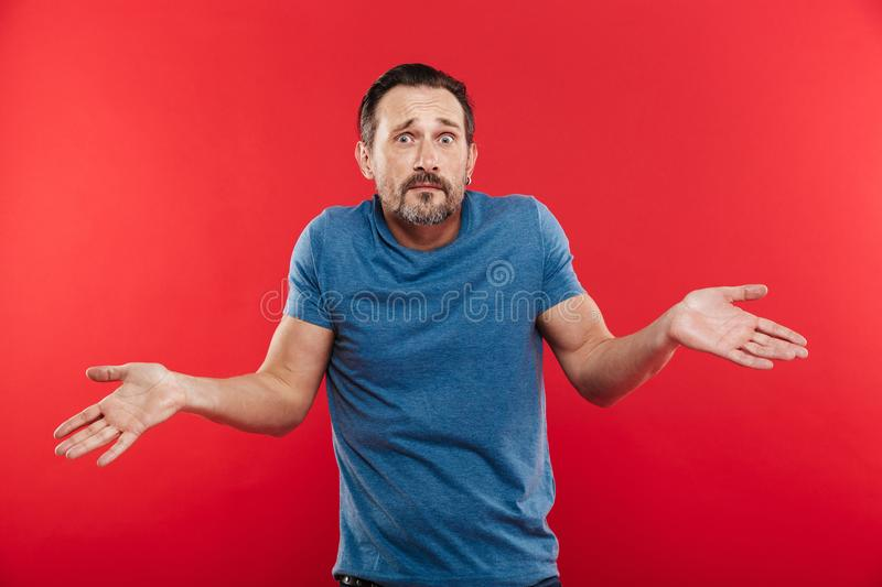 Portrait of caucasian adult man looking at camera expressing misunderstanding with throwing up hands, isolated over red background stock image