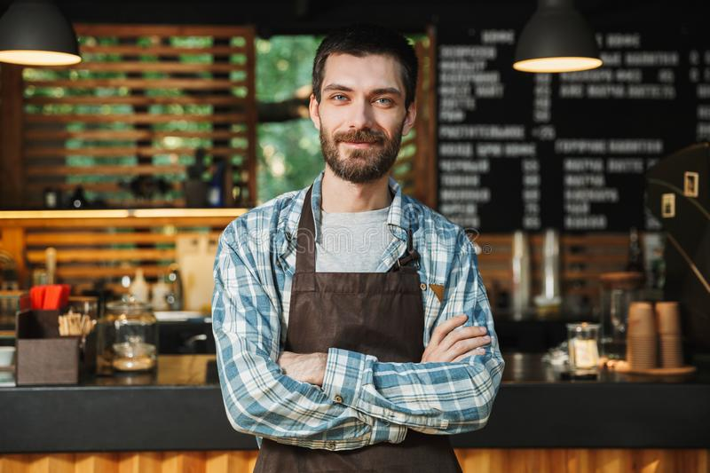 Portrait of caucasian barista guy standing with arms crossed in street cafe or coffeehouse outdoor. Portrait of caucasian barista guy wearing apron smiling and royalty free stock photos