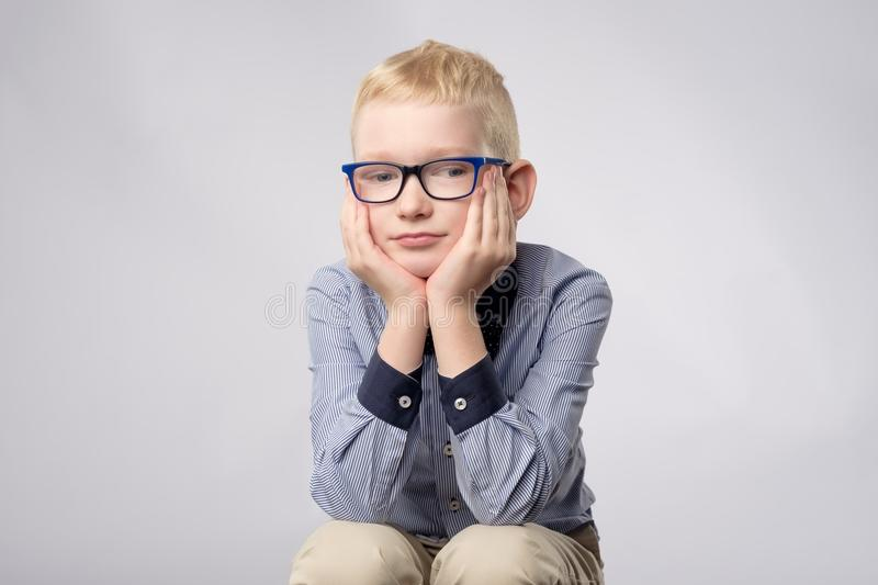 Portrait of caucasian blond boy in glasses looking with bored facial expression to camera on white background. royalty free stock images
