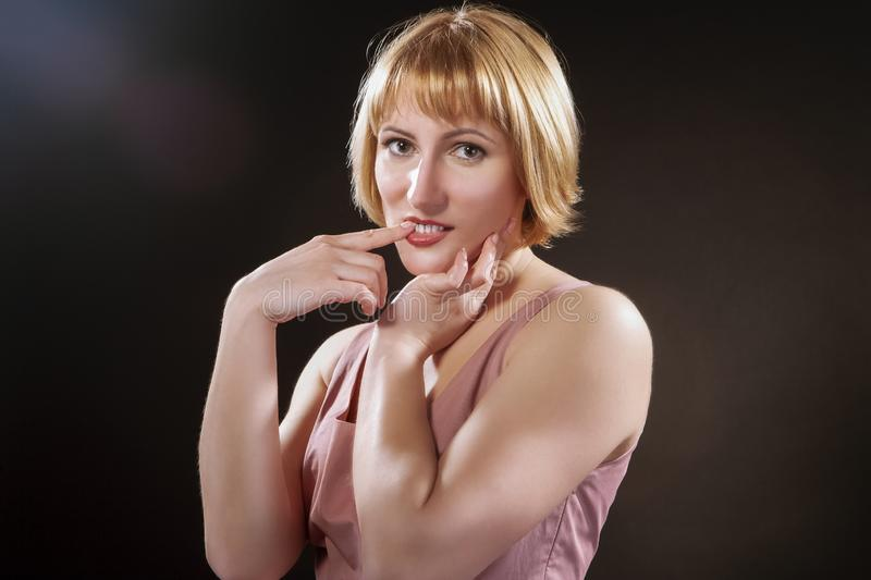 Portrait of Caucasian Blond Female in Pink Dress. Posing Against Black Background with Questioning Facial Expresison and Toching Teeth with Finger. Horizontal stock photo