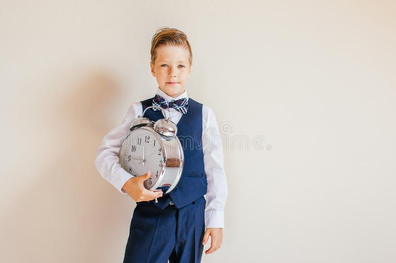Portrait of caucasian Boy in grey suit with big clock.Cute boy holding a Clock. Child back to school, on neutral background. royalty free stock images