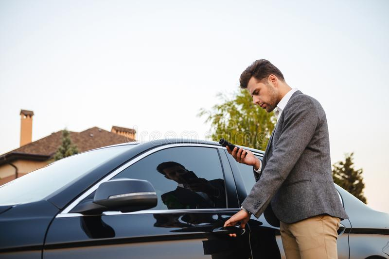 Portrait of caucasian businessman wearing suit, opening driver`s royalty free stock images