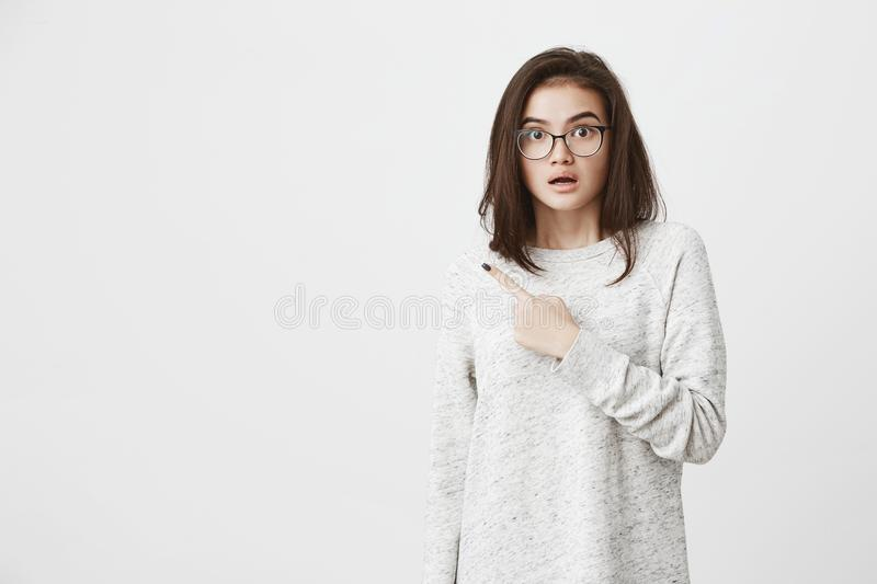 Portrait of caucasian cute brunette in glasses, lifting eyebrows in concern and shock, pointing index finger aside, over stock photography