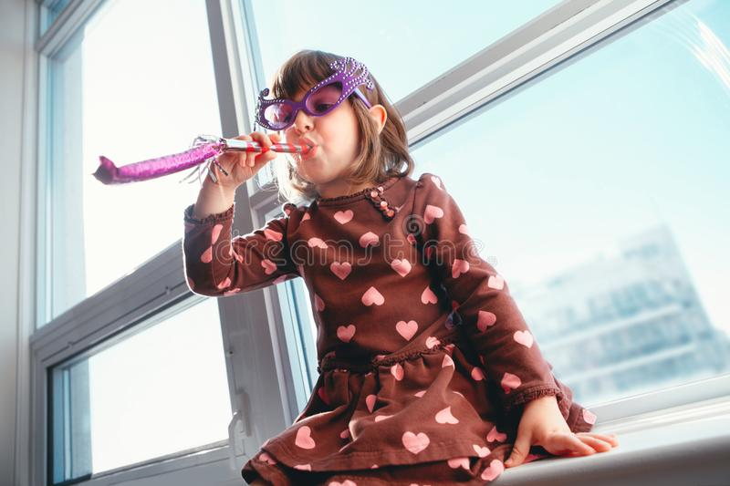 Girl child sitting on window sill at home and blowing whistle trumpet celebrating birthday stock photography