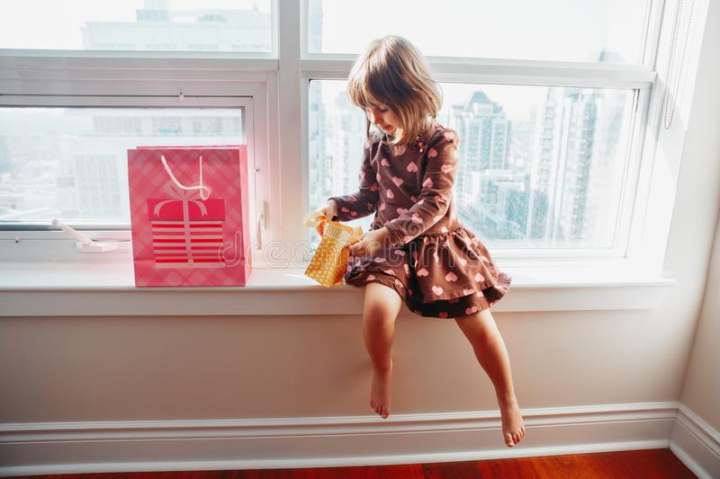 Girl child sitting on window sill at home opening birthday gifts royalty free stock photos