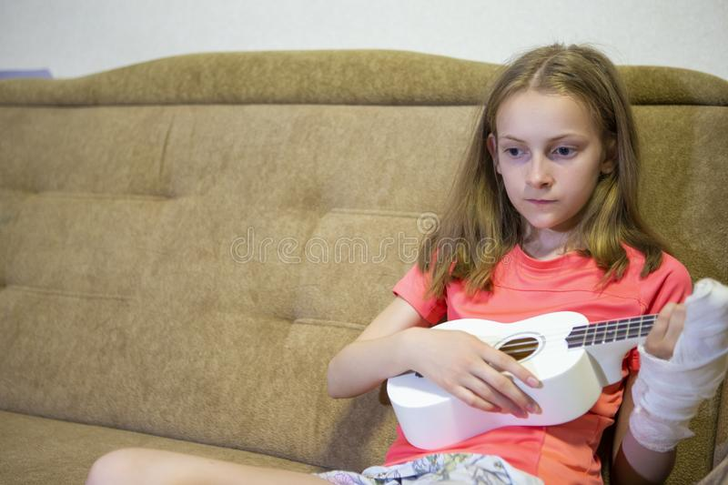 Portrait of Caucasian Girl  With Injured Hand In Plaster Playing hawaiian Guitar Indoors stock photos