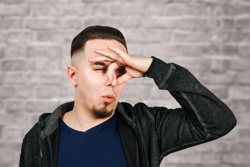 Portrait of Caucasian guy, close nose, stinks. Man on brick wall background. Portrait of Caucasian guy, close nose, stinks. Man on a brick wall background stock photos