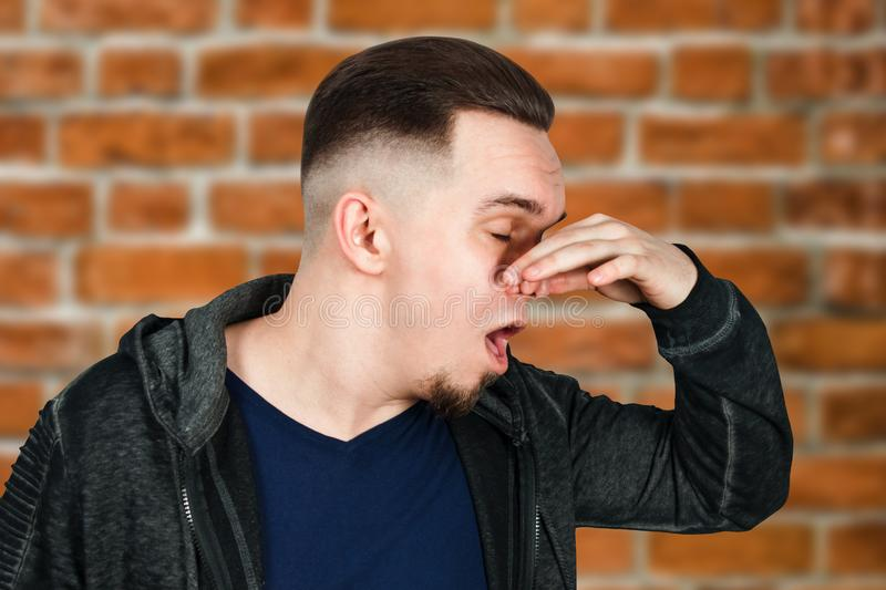 Portrait of Caucasian guy, close nose, stinks. Man on brick wall background. Portrait of Caucasian guy, close nose, stinks. Man on a brick wall background royalty free stock image