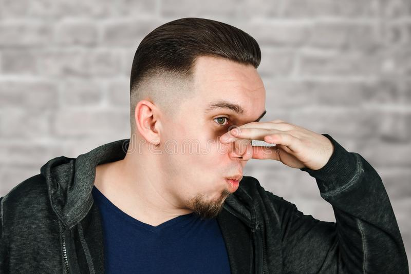 Portrait of Caucasian guy, close nose, stinks. Man on brick wall background. Portrait of Caucasian guy, close nose, stinks. Man on a brick wall background royalty free stock photography