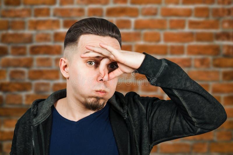 Portrait of Caucasian guy, close nose, stinks. Man on brick wall background. Portrait of Caucasian guy, close nose, stinks. Man on a brick wall background royalty free stock photos