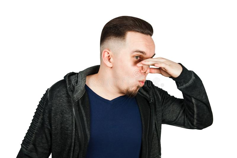 Portrait of Caucasian guy, close nose, stinks. Man isolated on white background. Portrait of Caucasian guy, close nose, stinks. Man isolated on a white royalty free stock image