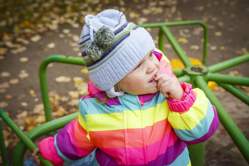 Portrait caucasian little baby girl in hat and jacket on carousel in autumn. A child looks at the sky. royalty free stock photography