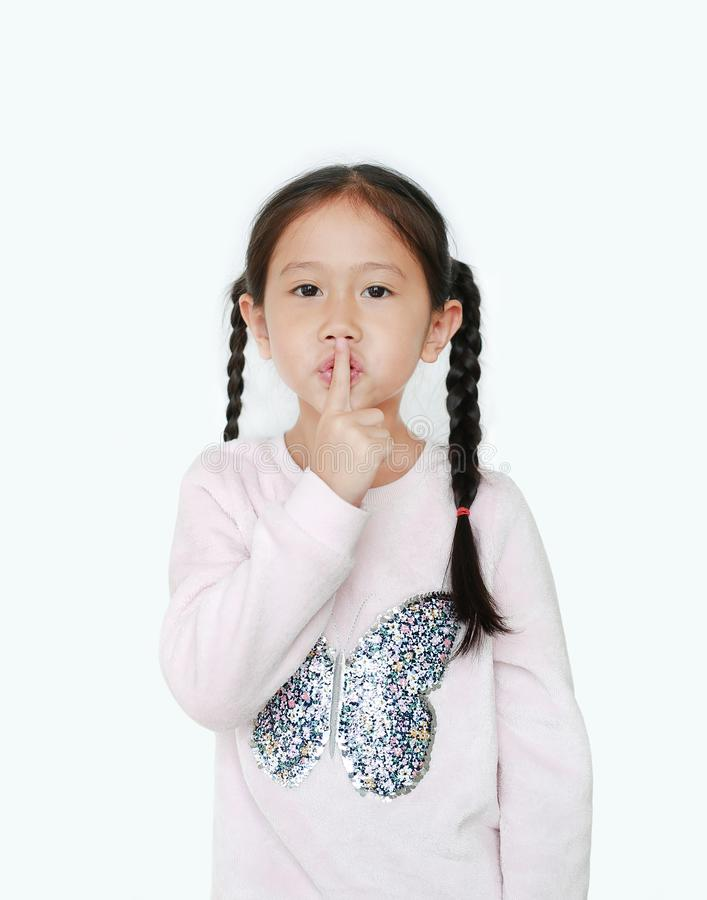 Portrait of caucasian little child girl with finger up to lips for making a quiet gesture isolated on white background. Kid stock image