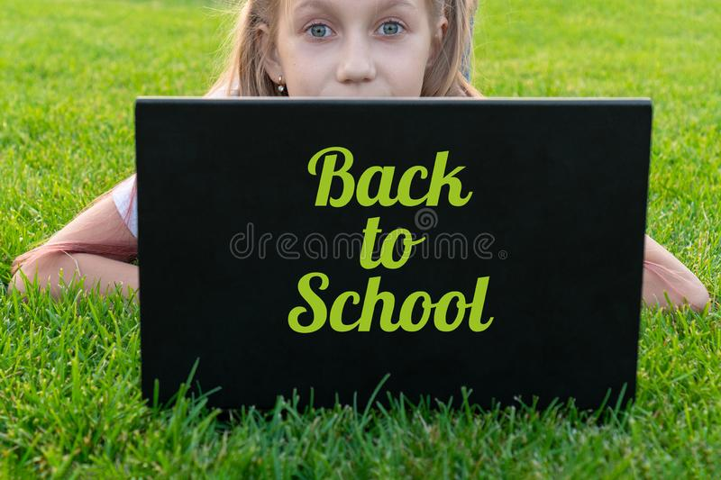 Portrait of caucasian little girl behind laptop computer lies on the grass in the park. Pretty girl enjoying modern generation stock photo