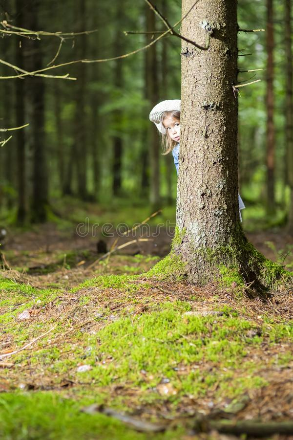 Portrait of Caucasian Little Girl Lurking Around the Tree. In Green Summer Forest. Vertical Image stock photography