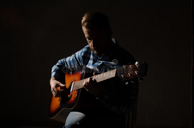 Portrait of Caucasian male musician playing guitar on stage, f. Ocus on hand stock photography