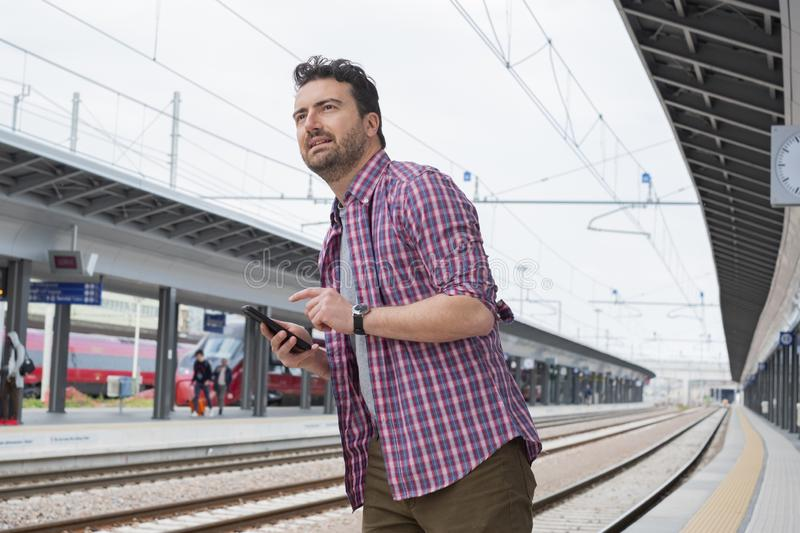 Portrait of caucasian male in railway train station. Man traveler backpacker waiting for train at train station stock photography
