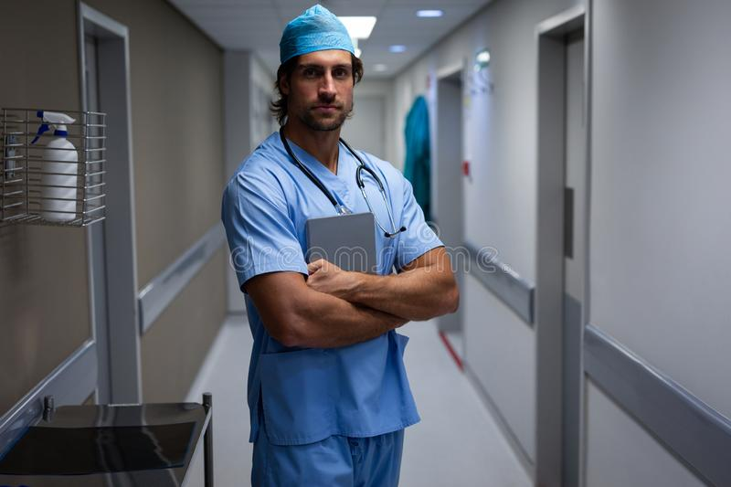 Male surgeon standing at hospital corridor stock photo